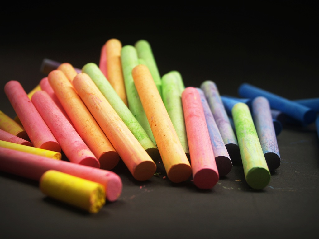 A pile of colorful chalk on a black background.